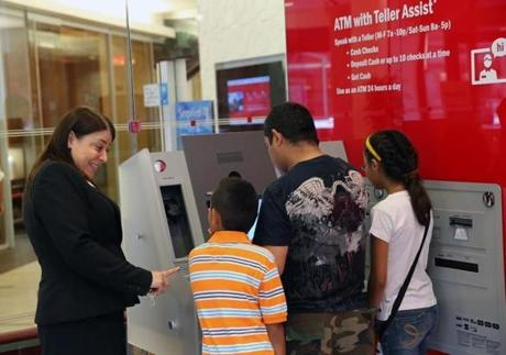 Bank of America's Jo Sears helped a customer navigate the new Teller Assist machine recently.